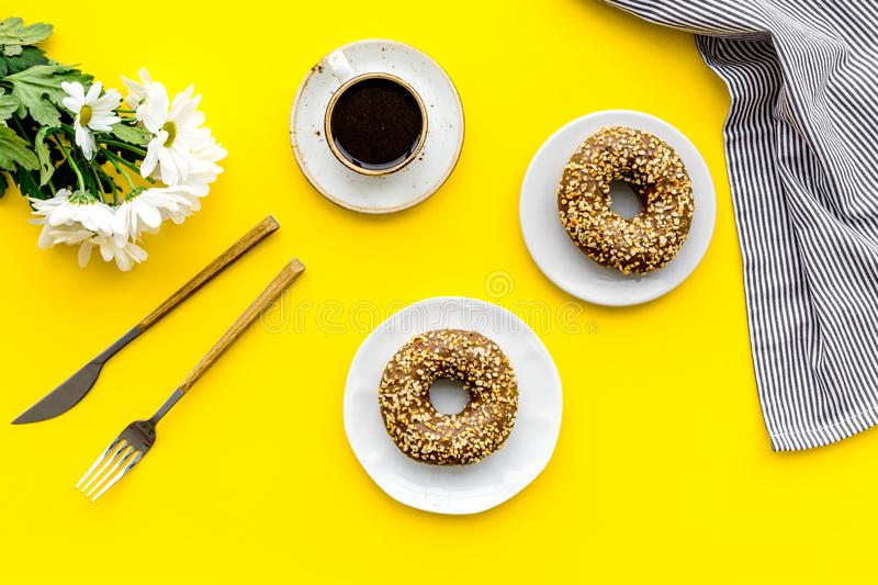 Modern breakfast desing with sweet donut, coffee and flowers on woman yellow desk background top view royalty free stock image