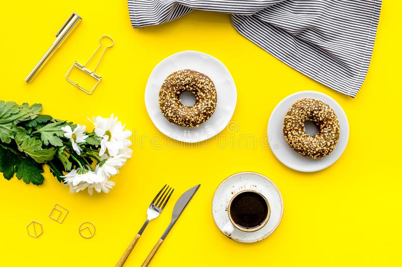 Modern breakfast desing with sweet donut, coffee and flowers on woman yellow desk background top view royalty free stock photos