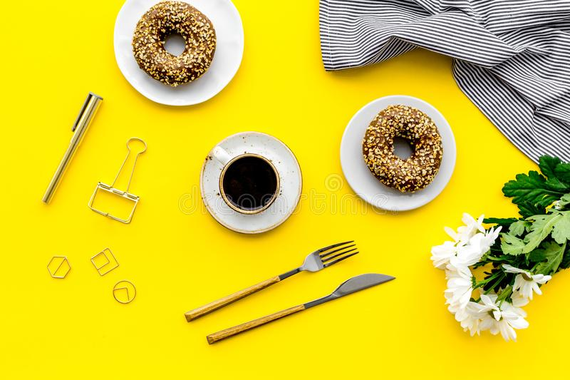 Modern breakfast desing with sweet donut, coffee and flowers on woman yellow desk background top view stock photos