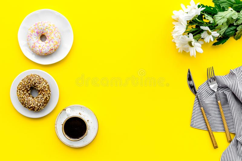 Modern breakfast desing with sweet donut, coffee and flowers on woman yellow desk background top view mock up royalty free stock photography
