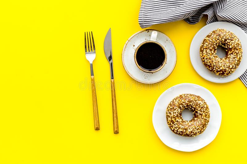 Modern breakfast desing with sweet donut, coffee and flowers on woman yellow desk background top view mock up royalty free stock photos