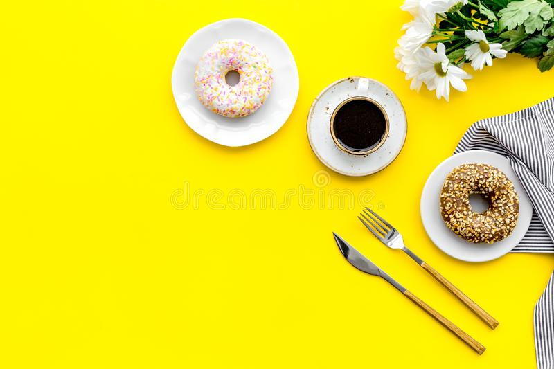 Modern breakfast desing with sweet donut, coffee and flowers on woman yellow desk background top view mock up stock photo