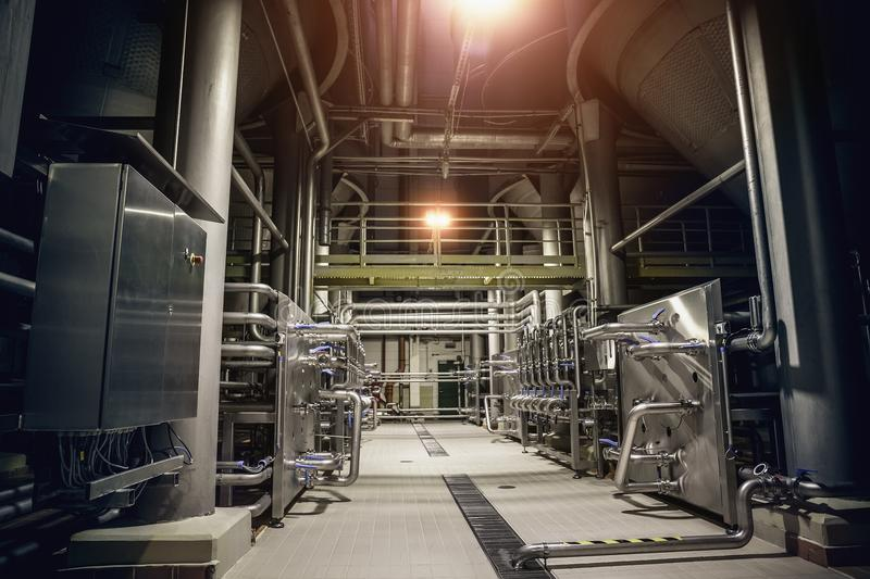 Modern brewery factory interior.Steel tanks or vats for filtration beer, pipe lines and other equipment tool in plant workshop. Industrial background royalty free stock photos