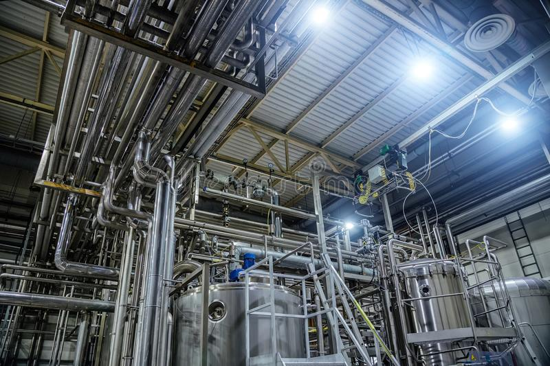 Modern brewery interior. Vats, pipeline, valves and other equipment of beer production line stock photography