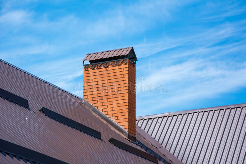 Modern brick chimney with forging and snow guards on rooftop under clear blue sky royalty free stock photos