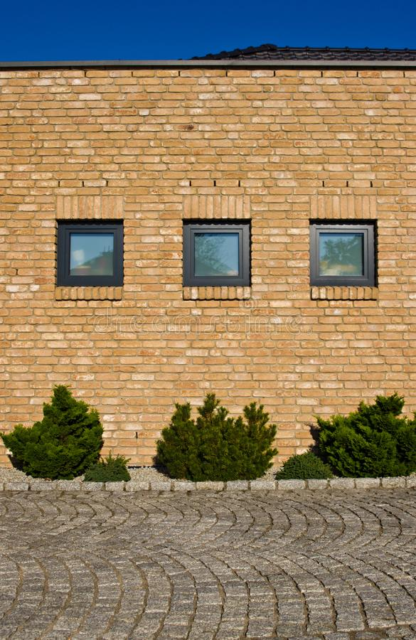 Modern brick wall with evergreen plants design stock photography