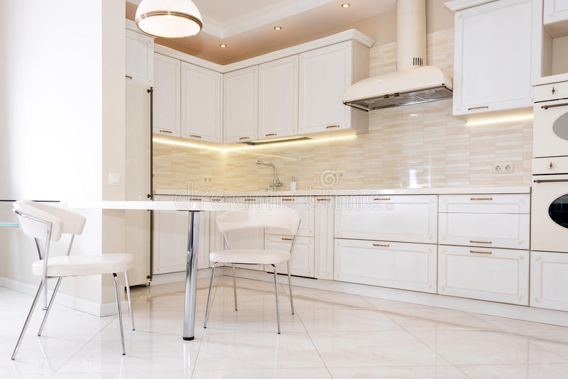 Modern, bright, clean kitchen interior in a luxury house. Interior design with classic or vintage elements. Practical. And well-furnished kitchen royalty free stock photo
