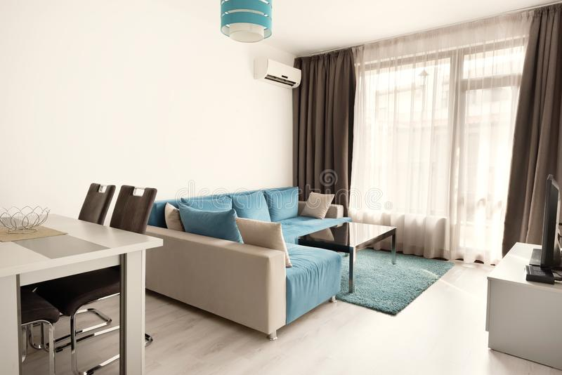 Modern bright and cozy living room interior design with sofa, dining table and kitchen. Grey and turquoise blue studio apartment.  stock images