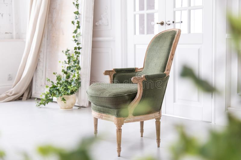 Modern, bright interior with stucco mouldings walls and a vintage armchair made of solid wood. Soft focus. stock photography