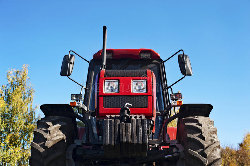 Modern bright red tractor outdoors. Modern bright red tractor on blue sky background royalty free stock image