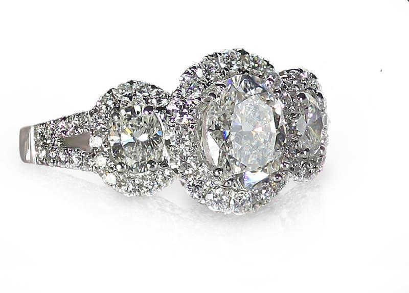 Modern Brilliant Cut three stone halo style diamond ring stock photo