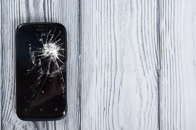 Modern broken mobile phone on white wooden background. Copy space. Top view stock photo