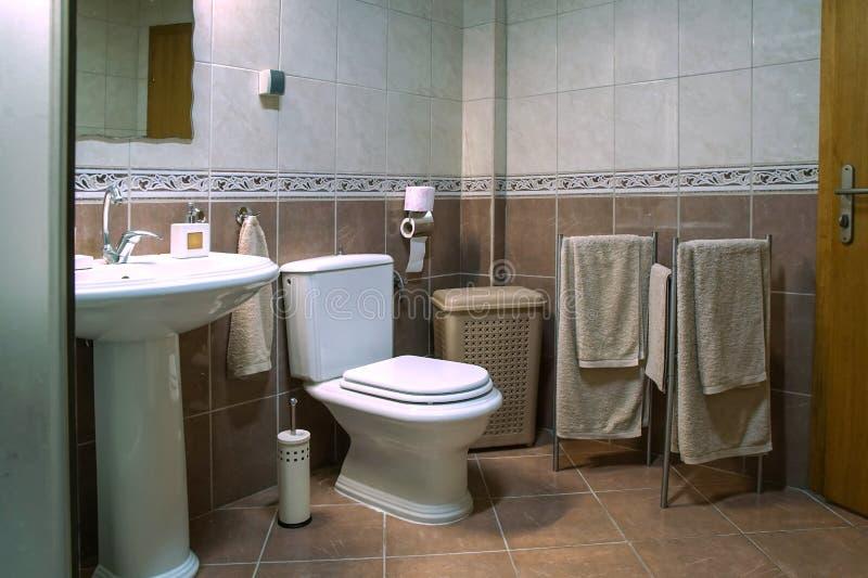 Modern brown bathroom with sink, toilet bowl, towels and brown tiles. Modern brown bathroom with sink, toilet bowl, towels and white and brown tiles stock photos