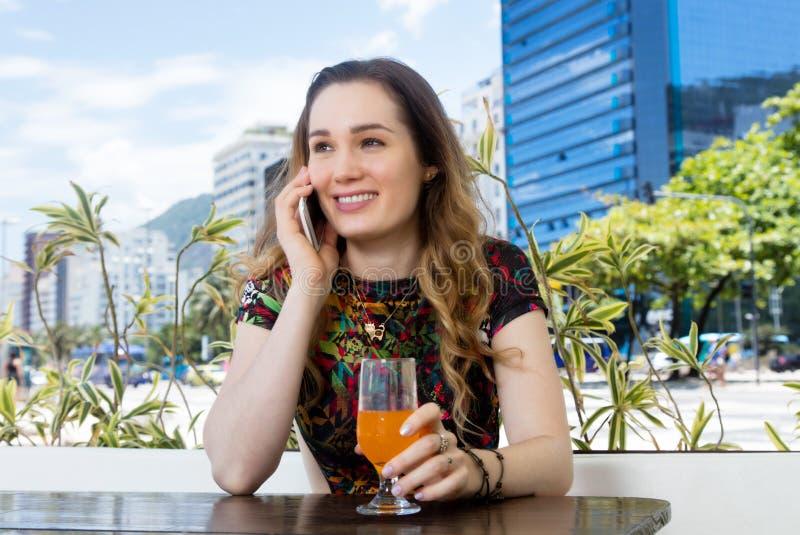Modern brunettkvinna som talar på mobiltelefonen i restaurang fotografering för bildbyråer