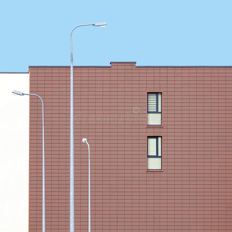Modern building facade with two windows and three street lamp posts. Abstract architecture picture royalty free stock photo
