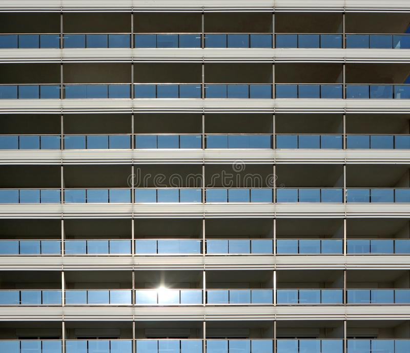 Modern building metal facade with rows of blue glass balconies stock image