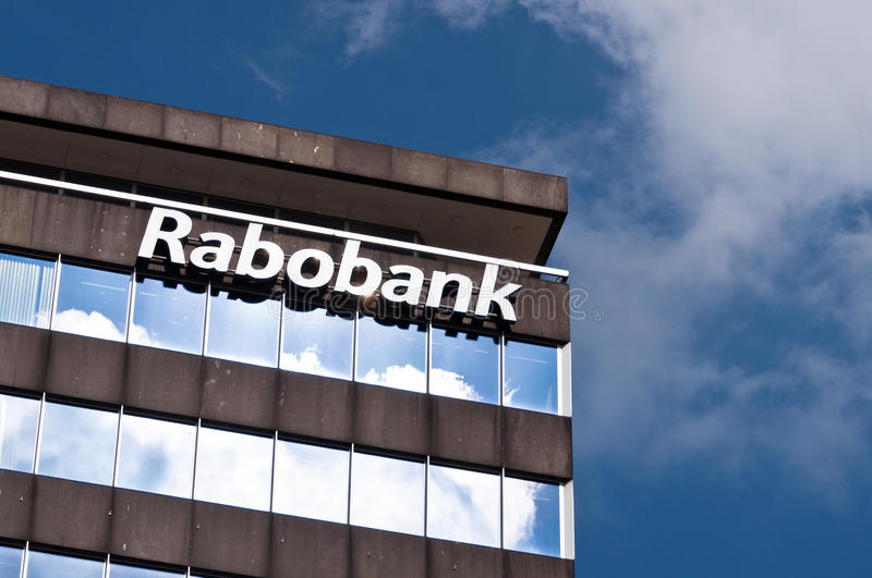 Modern building with Rabobank logo against blue sky with clouds. Eindhoven, Netherlands - July 26, 2013: Building with Rabobank logo. Rabobank is a Dutch bank stock photos