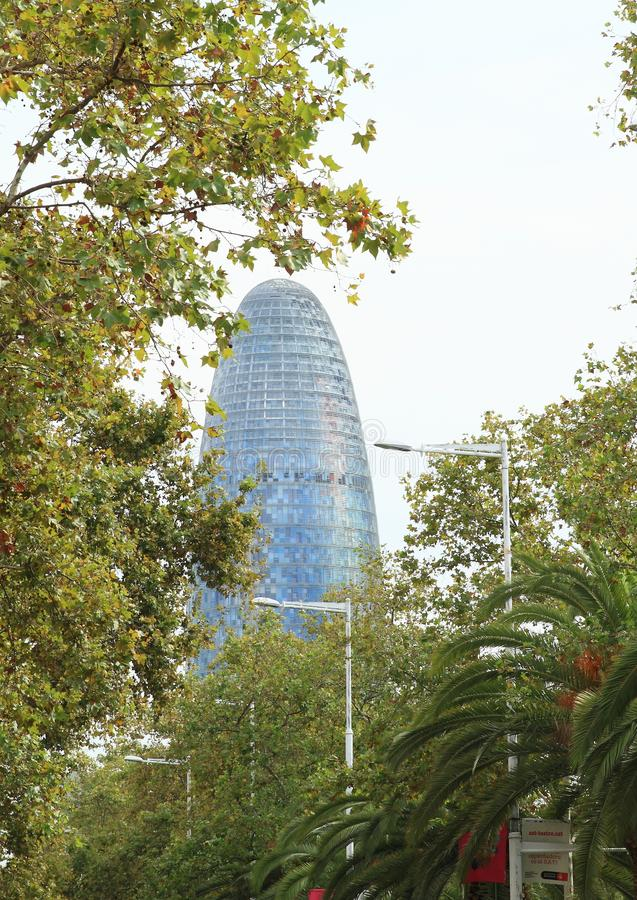 Torre Agbar in Barcelona. Modern building Torre Agbar or Torre Glòries behind trees in Barcelona, Spain royalty free stock images