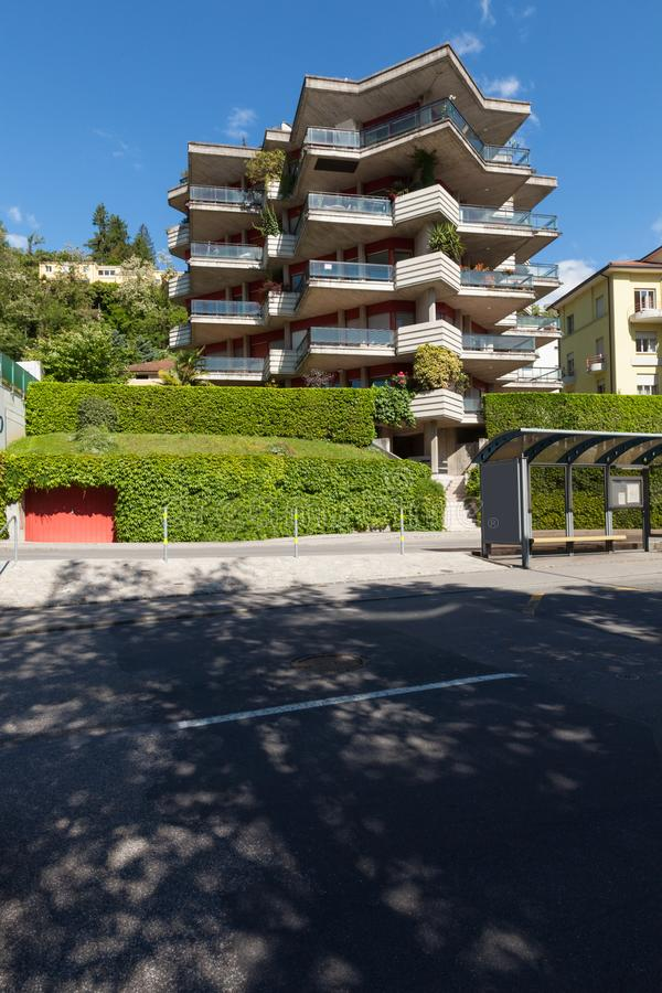 Modern building view from outside with road. Modern building view from oute. High green hedge. Summer sunny day royalty free stock photo