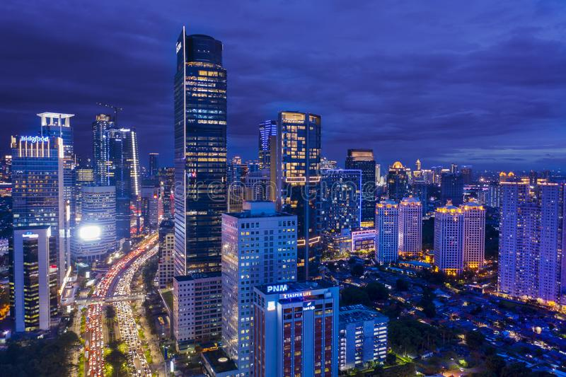 Modern buildings with rush hour traffic at evening. JAKARTA - Indonesia. January 03, 2019: Drone view of modern office buildings with rush hour traffic at stock images