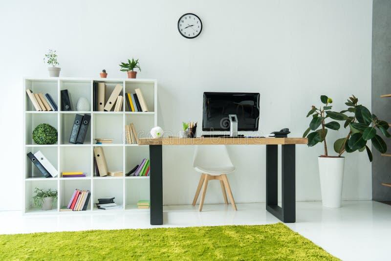 modern bureaubinnenland met computermonitor op lijst en boeken met omslagen stock afbeelding