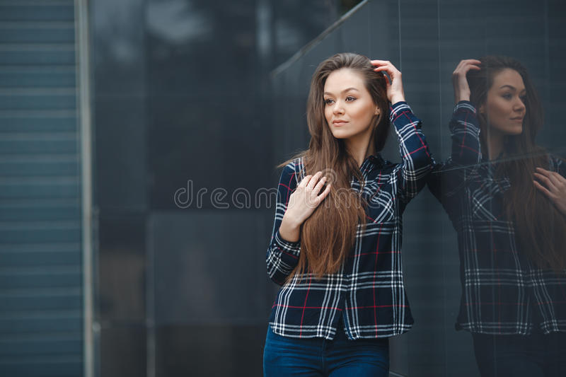 Modern business,a beautiful woman near the office is considering a business plan royalty free stock photo