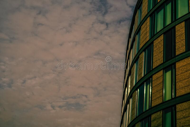 This is a modern business building. Below a cloudy winter sky stock images