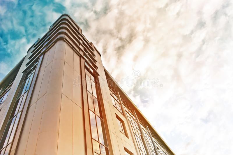 Modern business building for corporate constraction. Bottom view with blue sky, clouds and sinlight.  stock image