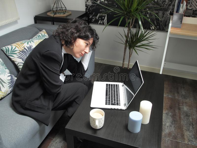 Modern business caucasian woman overwhelmed, sad, sitting on the sofa with a laptop and a cup of coffee stock image