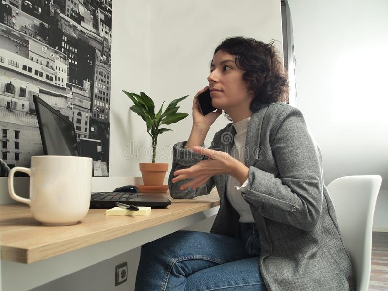 Modern business caucasian woman talking on the phone while is working on her laptop, she has post-its and a cup of coffee on her royalty free stock photo