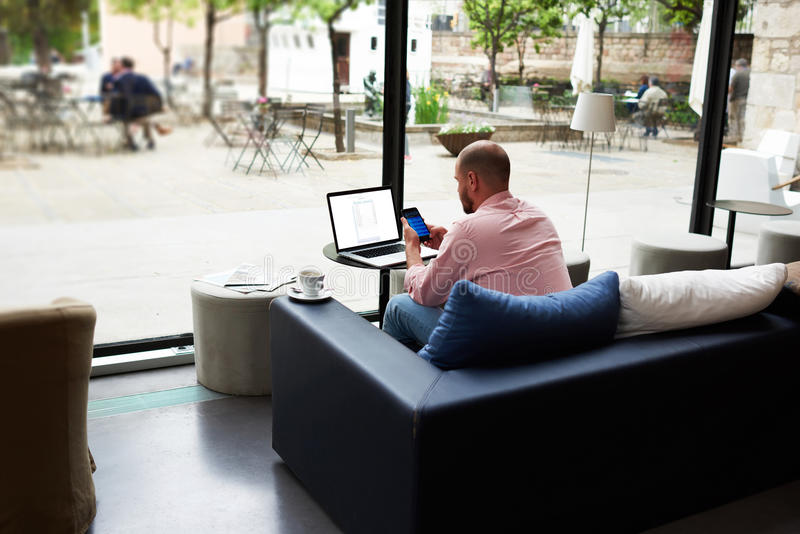 Modern business man busy working on smart phone and laptop computer. Young freelancer chatting on cell phone while sitting at sofa of coffee shop, entrepreneur royalty free stock photos