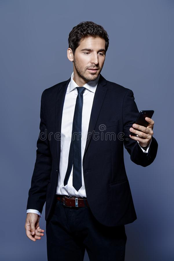 Modern business man. Contemporary businessman is talking on his cell phone. Business communications. Studio shot royalty free stock photo