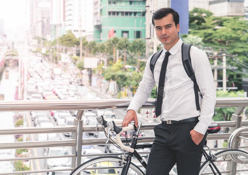 Modern Business man cycling bicycle to work to avoid traffic. Modern Business man is cycling bicycle to work to avoid traffic jam in busy city stock photos