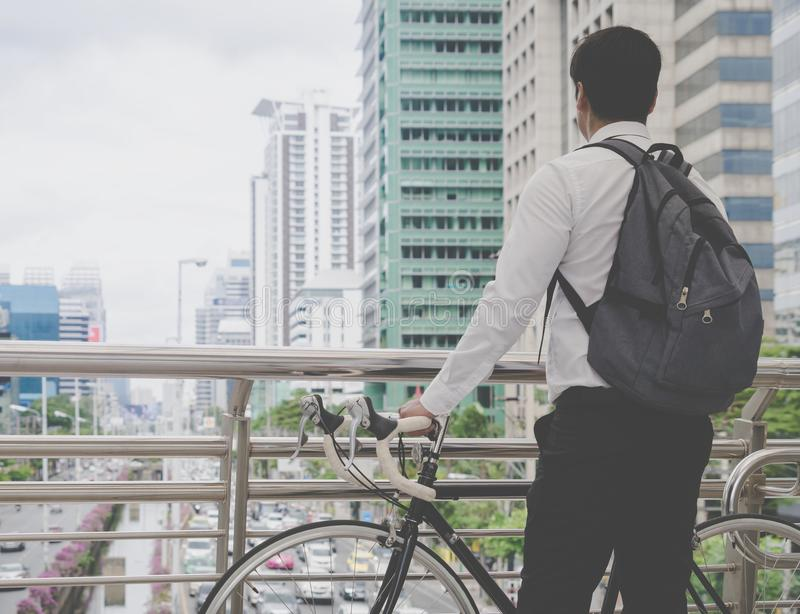 Modern Business man cycling bicycle to work to avoid traffic. Modern Business man is cycling bicycle to work to avoid traffic jam in busy city stock photo