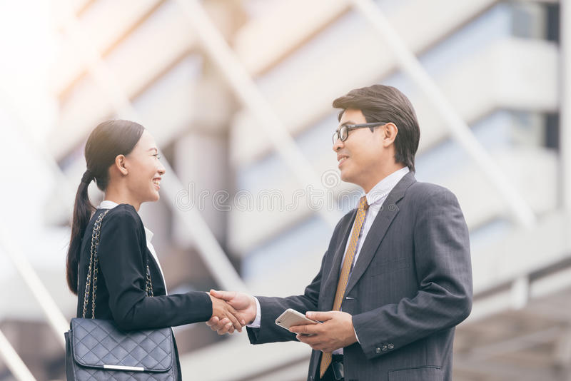 Modern Business people deal.partners shake hands, standing in front of his office. city background royalty free stock photography
