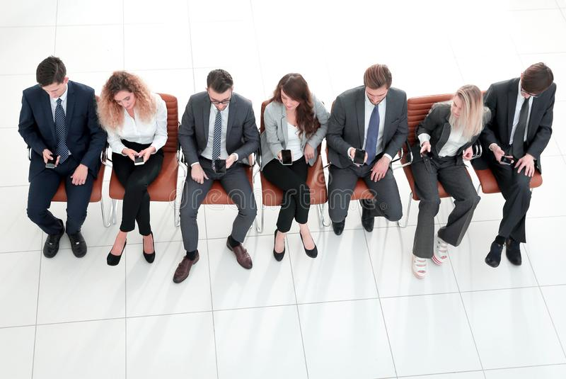 Modern business team using their smart phones. Isolated on a white background royalty free stock image