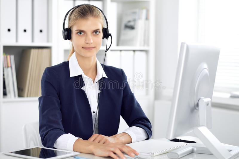 Modern business woman or confident female accountant in headset in office communicating with desktop pc. Student girl. During exam preparing. Audit, tax service royalty free stock photo