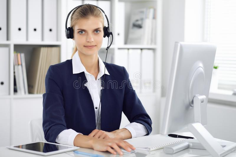 Modern business woman or confident female accountant in headset in office communicating with desktop pc. Student girl royalty free stock images