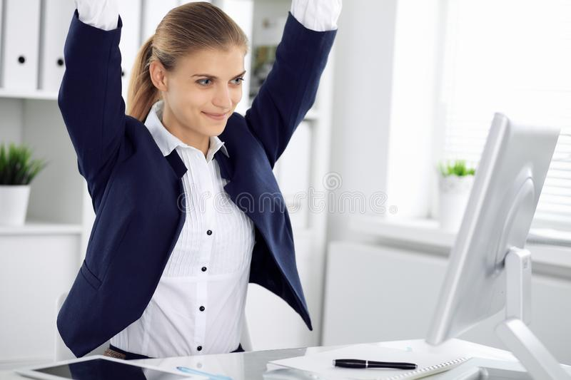 Modern business woman or confident female accountant in office with arms raised represents success at work. Student girl. During exam preparing. Audit, tax stock photography