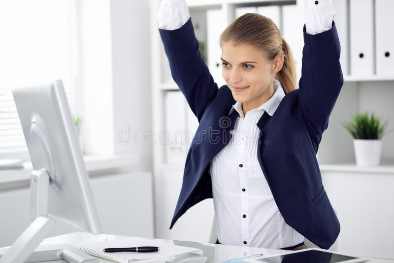 Modern business woman or confident female accountant in office with arms raised represents success at work. Student girl royalty free stock photography