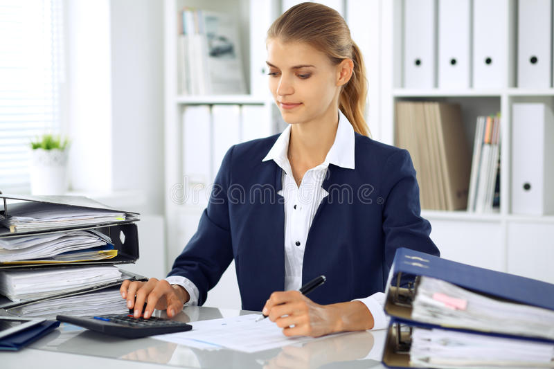 Modern business woman or confident female accountant in office. Student girl during exam preparing. Audit, tax service. Or education concept royalty free stock photo