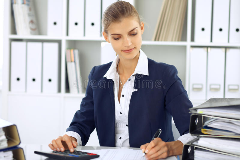 Modern business woman or confident female accountant in office. Student girl during exam preparing. Audit, tax service. Or education concept stock photography