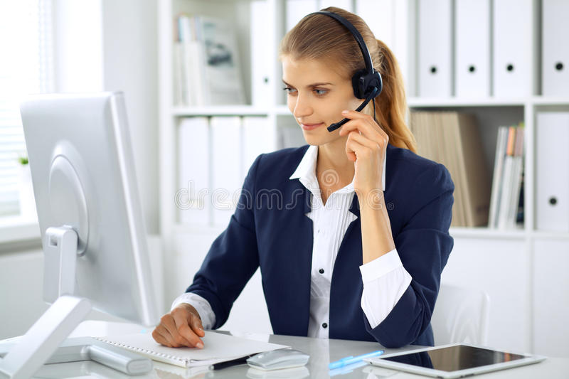Modern business woman with headset in the office. Customer service operator at home work place. Success start up concept. Modern business woman or student girl stock photo