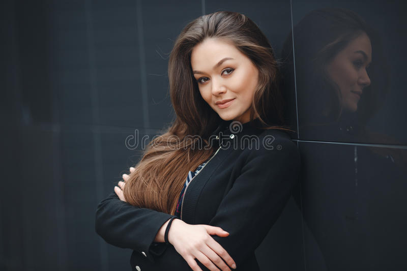 Modern business, woman near the office ponders business plan. A young leader, a beautiful modern woman, a brunette with long straight hair and brown eyes, long stock photo
