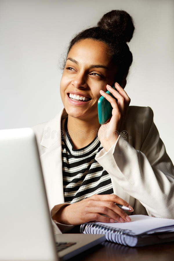 Modern business woman smiling and talking on cellphone. Portrait of modern young business woman smiling and talking on cellphone royalty free stock photography