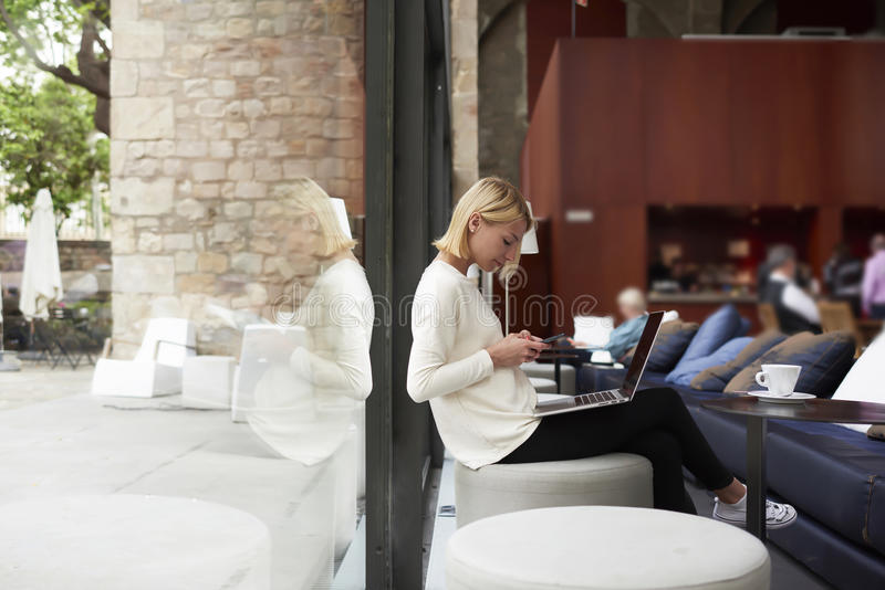 Modern business woman working on her net-book sitting at library or loft studio with big windows. Female freelancer connecting to wireless via smartphone while