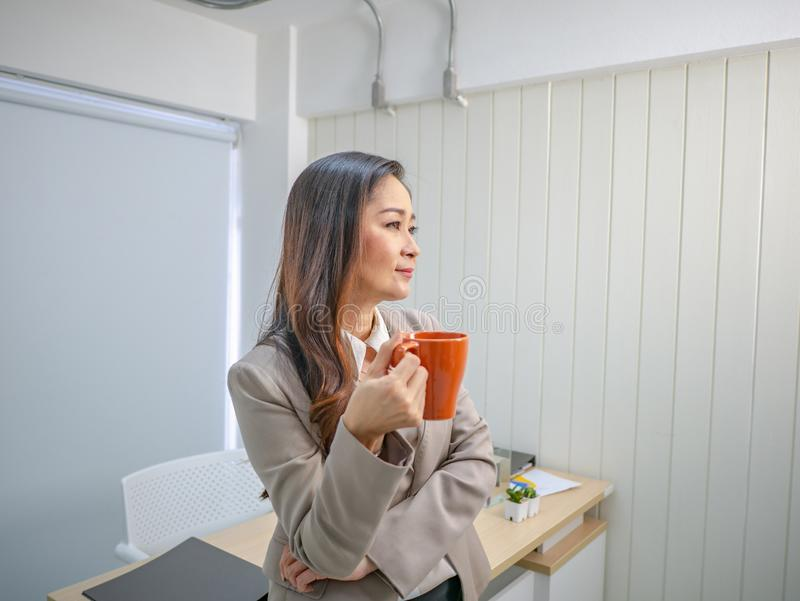 Modern business women hold her coffee cup or mug in the office stock photography