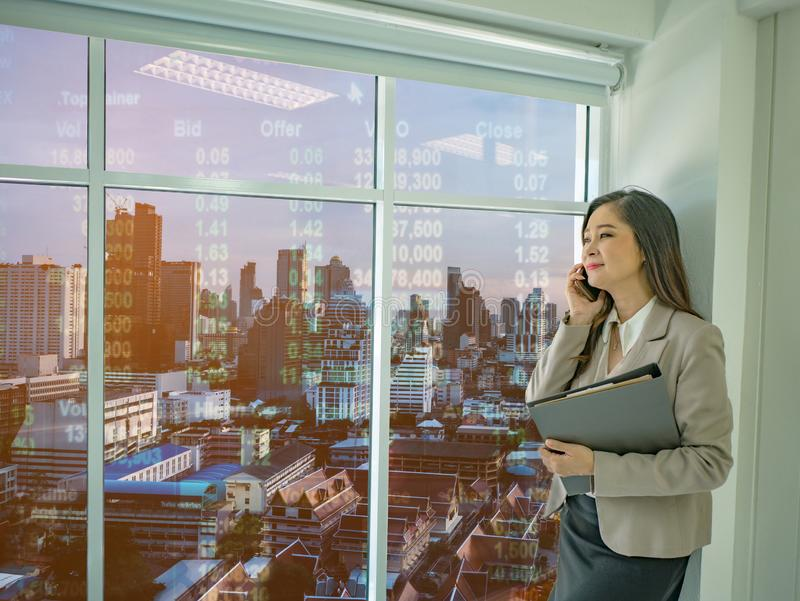 Modern business women use mobilephone talk about stock market white looking out of the window in her office stock photography
