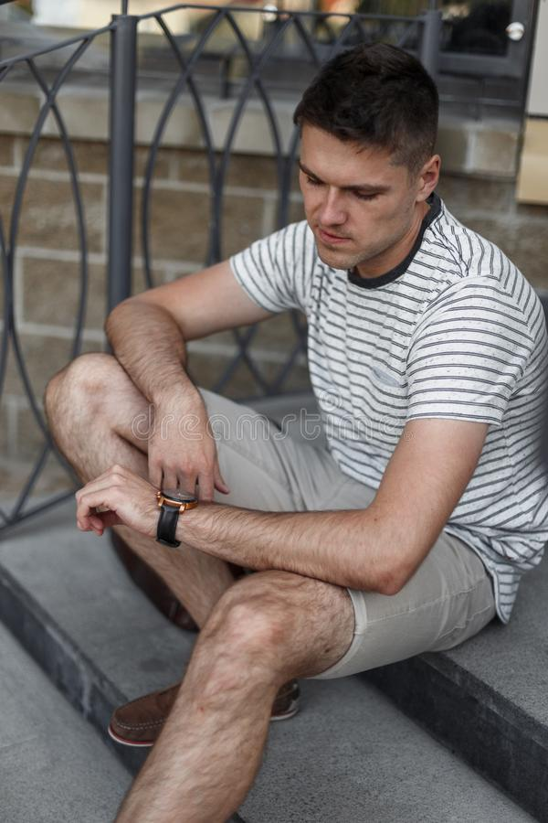 Modern business young man in stylish summer clothes sits on a stone staircase and looks at clock. Attractive manager guy resting stock photo