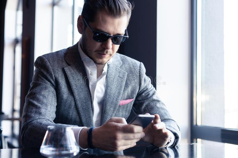 Modern businessman drinking espresso coffee in the cafe during lunch time and using mobile phone. stock photos